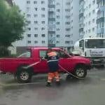 """VIDEO: Angajații Supercom spală prin parcări mașinile """"de șmecheri"""". Cu cisterna!  Credeți că Primăria Bistrița îi va amenda?"""